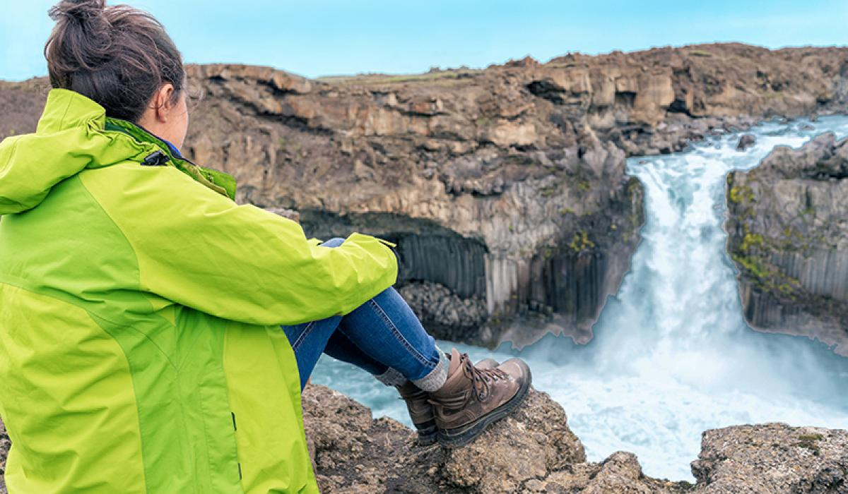 BilFERIE PÅ ISLAND_Klassisk bilferie rundt Island_Dame nyter den islandske naturen © Din Islandsreise